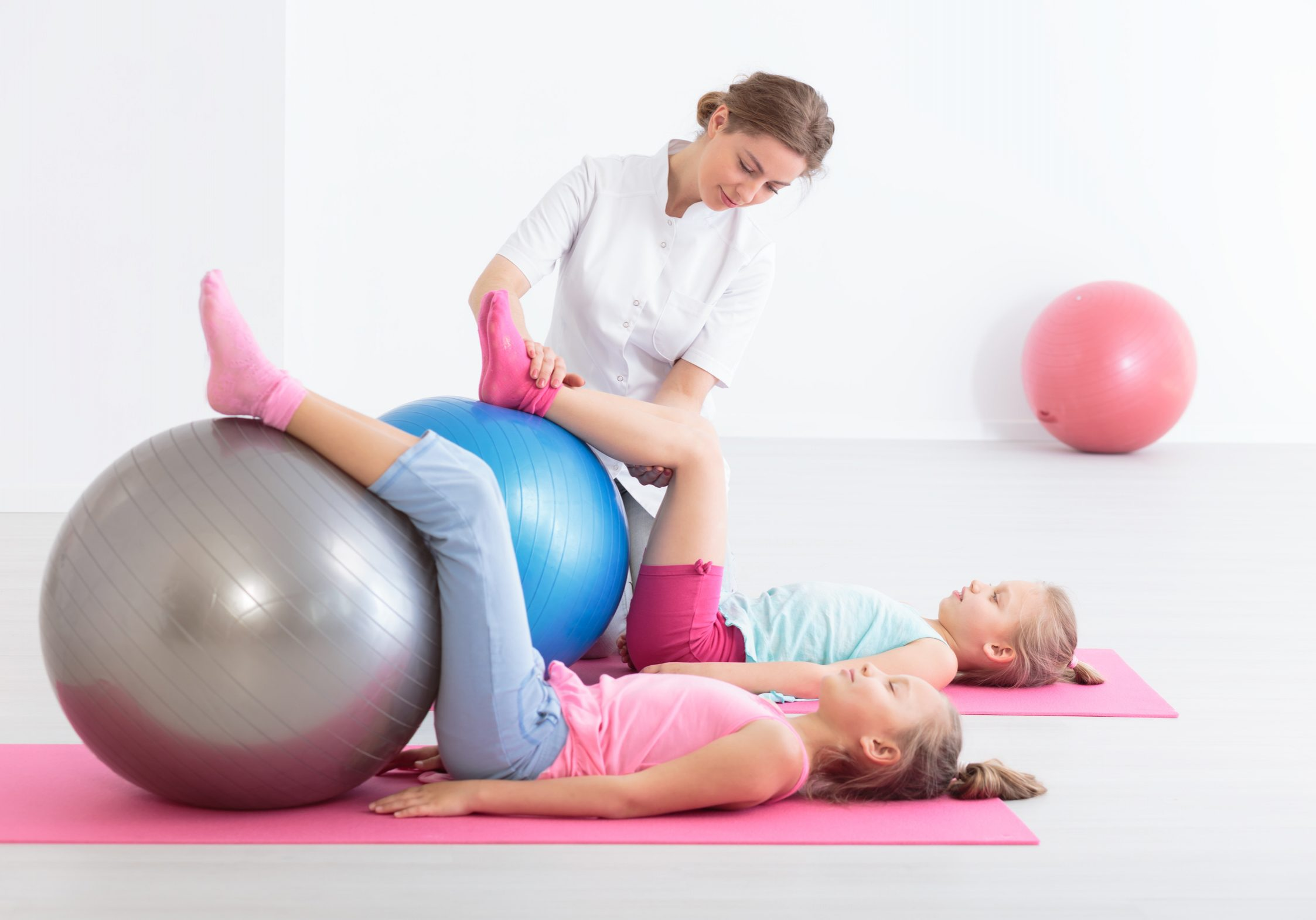 Two school girls lying on exercise mats exercising their legs on balls, accompanied by a physical therapist